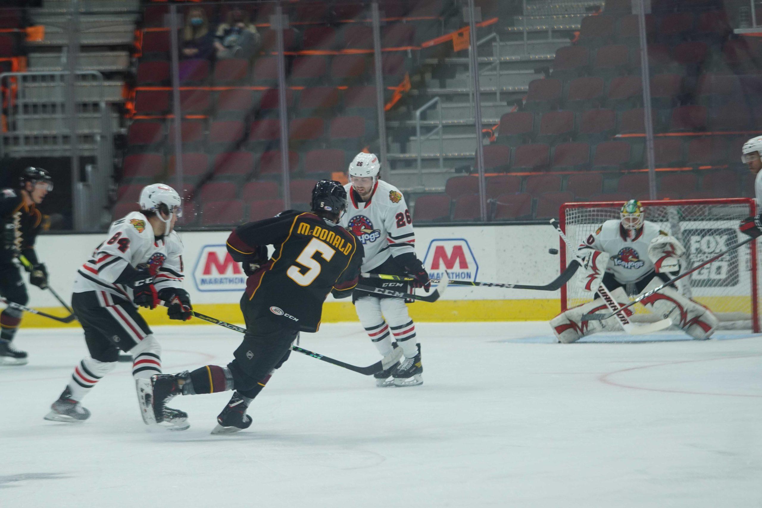 Cleveland Monsters defenseman shoots on Rockford IceHogs goaltender Collin Delia.